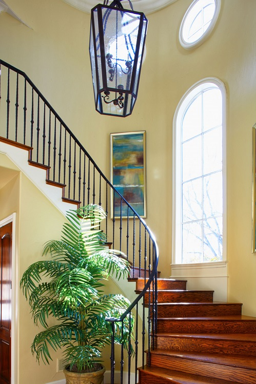 The previous homeowner had tapestries hanging in the stairwell. We decided to update with paintings commissioned to be proportionate in the space. The 7.5' palm tree softens the stairwell and brings nature indoors.